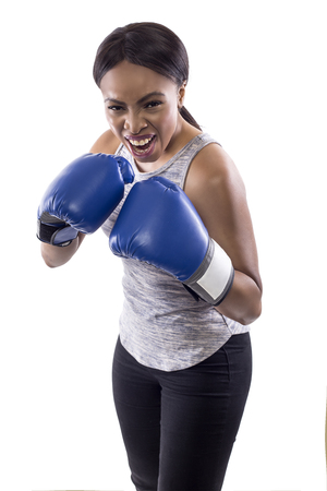 Black female on a white background wearing boxing gloves yelling angry.  Part of image set for gritty woman series.