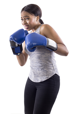 Black female on a white background wearing boxing gloves looking scared.  Part of image set for gritty woman series. Stock Photo
