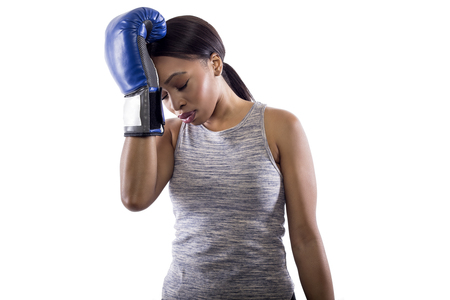 Black female on a white background wearing boxing gloves disappointed with a mistake.  Part of image set for gritty woman series.