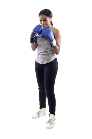 Black female on a white background wearing boxing gloves looking nervous.  Part of image set for gritty woman series. Stock Photo