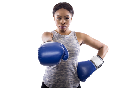 Black female on a white background wearing boxing gloves pointing forward.  Part of image set for gritty woman series.