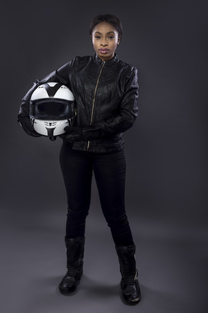 Black female motorcycle biker or race car driver or stuntwoman wearing leather racing suit and holding a protective helmet.  She is standing confidently in a studio Stock Photo