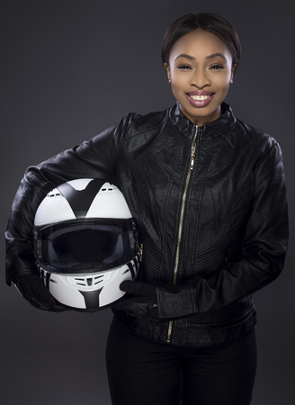 Black female motorcycle biker or race car driver or stuntwoman wearing leather racing suit and holding a protective helmet.  She is standing confidently in a studio Stockfoto