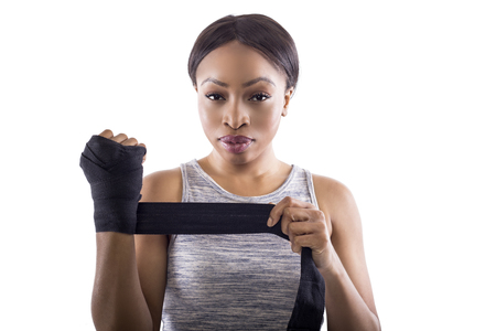 Black female fighter or boxer preparing by wearing gloves and wrapping wrist. Isolated on a white background.  She is dressed in a modest athletic outfit.  The image depicts self defense and sports. Stock fotó