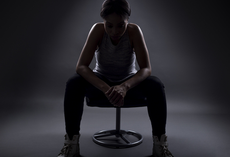 Silhouette of black female athelte sitting to rest or preparing for a competition or upset over losing and failing at sports. The woman looks gritty on dark background.