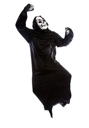 Halloween costume of a skeleton grim reaper wearing a black robe on a white background acting happy or joyful