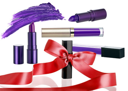 Arrangement of lipstick makeup cosmetics as a holiday gift set.  These products have a ribbon or bow to show they are on a seasonal Christmas sale.  Isolated on a white background.