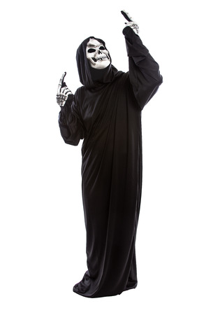 Halloween costume of a skeleton grim reaper wearing a black robe on a white background presenting or advertising something Stock Photo