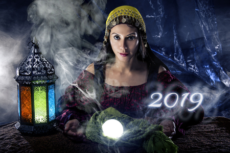 Female fortune teller or psychic reading with a cystal ball predicting the future of the year 2019 Stock Photo