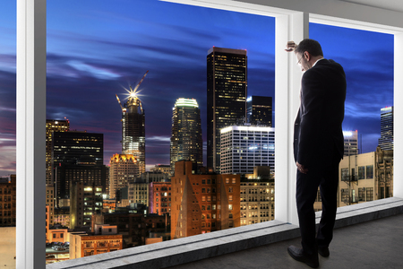Middle aged businessman looking out a bright office window and thinking in city of LA Imagens