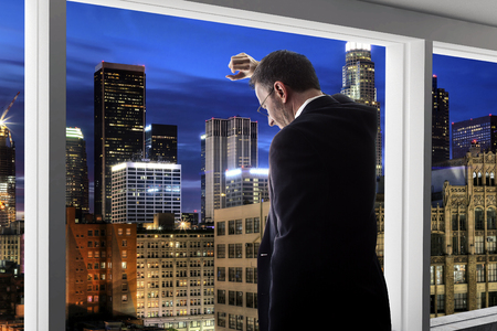 Middle aged businessman looking out a bright office window and thinking in city of LA Foto de archivo