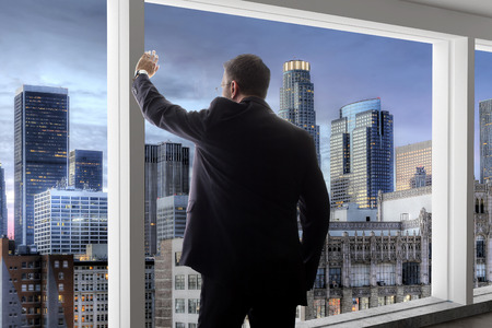 Middle aged businessman looking out a bright office window in Los Angeles and thinking
