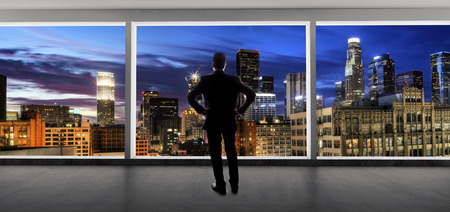 Middle aged businessman looking out a bright office window and thinking in city of LA 免版税图像