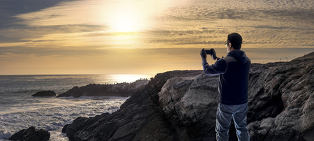 Tourist doing mobile photography with a cell phone standing on the rocks along the Malibu beach coastline in California during sunset. Stock Photo