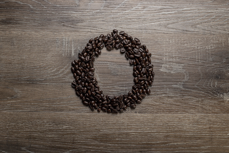 Dark roasted coffee bean arranged on a wooden table in the shape of text alphabet letter O Imagens