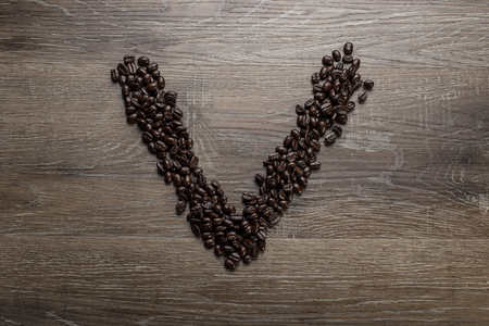 Dark roasted coffee bean arranged on a wooden table in the shape of text alphabet letter V