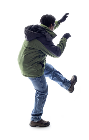 Mountain climber or hiker isolated on a white background for composites.  The man is acting like he is climbing something and depicts adventure and extreme sports. Standard-Bild