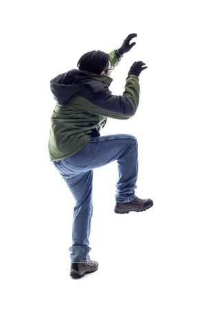 Mountain climber or hiker isolated on a white background for composites.  The man is acting like he is climbing something and depicts adventure and extreme sports. Stock Photo