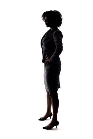 Silhouette of a Black Businesswoman posing as a confident leader or arrogant person.  She is isolated on a white background