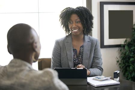 Zwarte vrouwelijke zakenvrouw in een kantoor met een klant die juridisch advies geeft over belastingen of financiële leningen. De vrouw kan een advocaat of een cpa-accountant zijn.