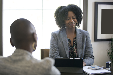 Couple of black female businesswomen or partners arguing at work or a bossy manager doing a job interview or perfomance review to an employee and looking disappointed.  Stock Photo