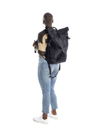 Femme afro-américaine noire portant un sac à dos regardant un fond blanc pour les composites. Elle est debout comme si elle était une touriste ou une randonneuse en trekking. Banque d'images