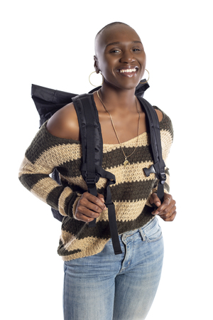 Black African American female wearing a backpack isolated on a white background.  She is standiing like she is a tourist or a hiker trekking.