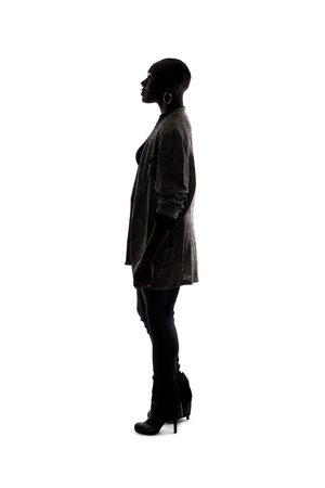 Black female African American model silhouette on a white background.  She is posed standing or waiting in side view. Stock Photo