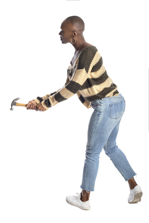 Black African American female swinging a hammer pretending to hit or smash on a white background.  She is destroying or repairing something.  Depicts DIY home improvement or feminist self reliance.