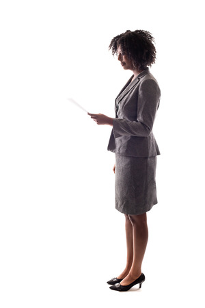 Side View of a Black Businesswoman reading a document, report or resume.  She could also be giving a speech and reading a script like a candidate.