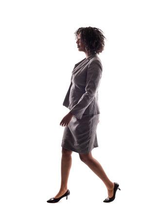 Vista laterale di una donna d'affari nera che cammina in vista laterale isolata su uno sfondo bianco. Archivio Fotografico