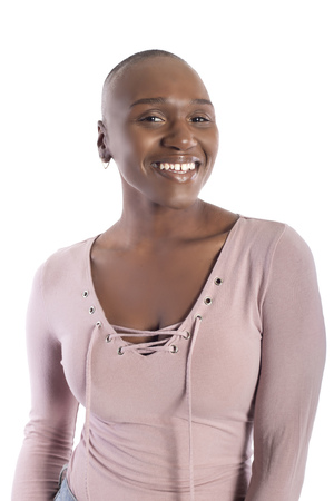 Black african american female model with bald hairstyle wearing a pink shirt on a white background looking happy and smiling