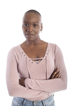Black african american female model with bald hairstyle wearing a pink shirt on a white background looking confident or arrogant