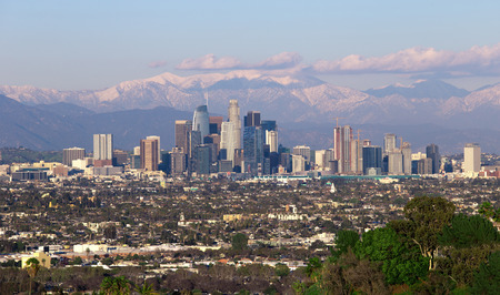 Panoramic view of the city of Los Angeles California with snowy mountain caps showing the end of the drought due to climate change. The wide view shows Hollywood and Downtown.