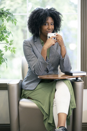 Black African American female as an adult student drinkling coffee before reading a book to study.  The intelligent woman can also be a teacher getting ready in the morning.