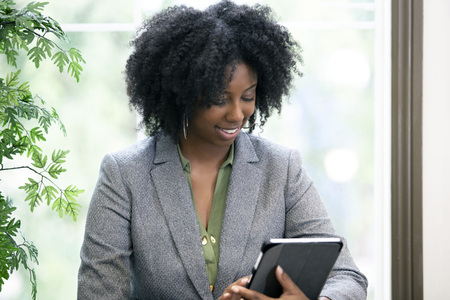 Black African American female as an adult student taking an online course and browsing with a tablet.  She is taking online school or doing research as a businesswoman. Imagens
