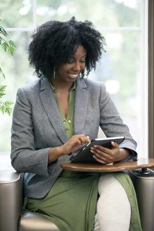 Black African American female as an adult student taking an online course and browsing with a tablet.  She is taking online school or doing research as a businesswoman. 版權商用圖片