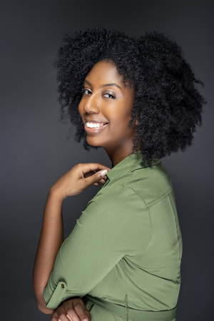 Black African American fashion model posing with afro hairstyle on a gray studio background.  She is confident and smiling showing off the ethnic curly haircut.