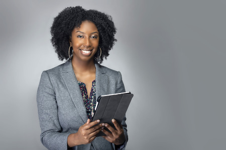 Black African American teacher or businesswoman sitting and holding a tablet computer.  The confident female author or writer looks like she is preparing for a seminar or as a keynote speaker. Imagens