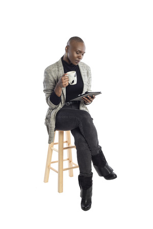 Black African American businesswoman or writer as a keynote speaker for a seminar preparing for the presentation with a tablet and coffee. Stockfoto
