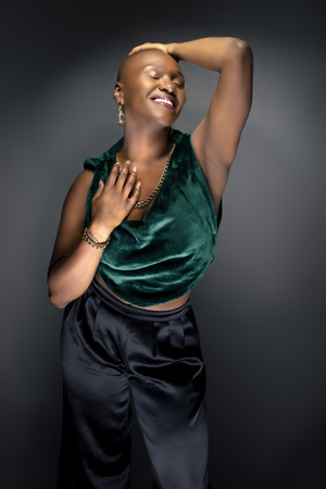 Black African American female fashion model posing with bald hairstyle and green trendy clothing.  Her bold modern look and muscular and fit body represents a strong and confident woman.