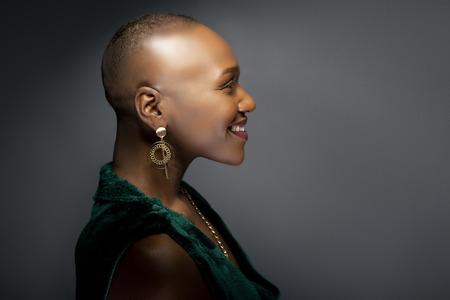 Schwarzes afroamerikanisches weibliches Modemodell mit einer kahlen Frisur in einem Studio. Das Porträt zeigt die Schönheit und das Selbstbewusstsein der kühnen und trendigen Glamour-Frisur. Standard-Bild