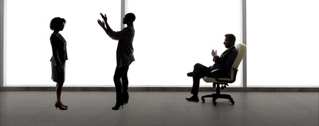 Black African American actress and scene partner auditioning for a role to a male casting director in a studio. The actors are silhouettes and depicts the Hollywood entertainment industry. Stockfoto