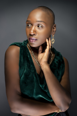 Beautiful black African American female model posing confidently with bald hairstyle in a studio.  The woman is wearing stylish fashion and portraying uniqueness and individuality.