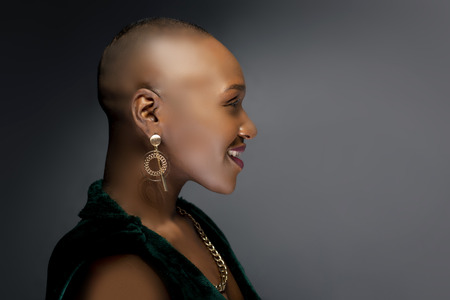 Black African American female fashion model with a bald hairstyle in a studio.  The portrait shows the beauty and confidence of the bold and trendy glamour hairdo style. Banco de Imagens - 122768940