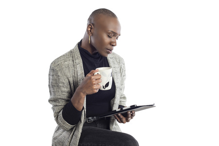 Black African American businesswoman or writer as a keynote speaker for a seminar preparing for the presentation with a tablet and coffee. Stockfoto - 122768980