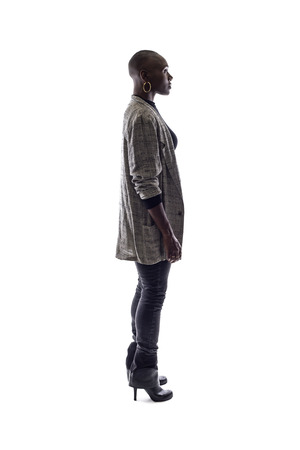 Black female African American model on a white background.  She is posed standing or waiting in side view.