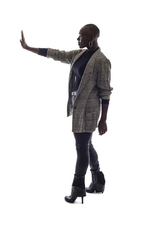 Black female African American model on a white background.  She is holding hands up in a stop gesture
