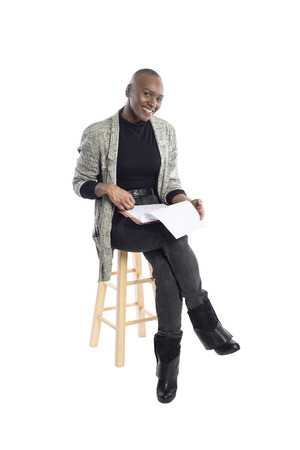 Black African American businesswoman reading contracts or reports or a teacher preparing her lessons for a class or seminar. She is sitting and isolated on a white background with paperwork.