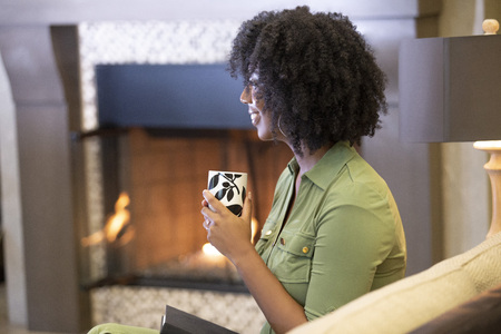 Black African American woman resting at home drinking coffee or CBD tea while relaxing on a couch by a fireplace.  She is holding a warm cup in a living room.